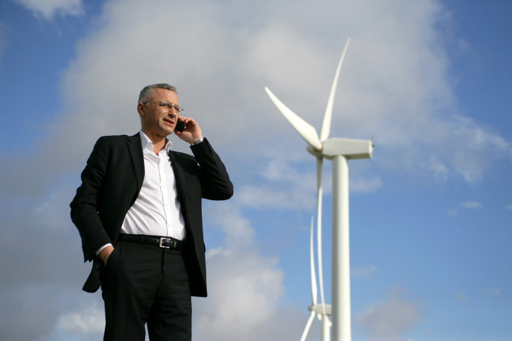 Happy Man on mobile phone next to wind turbine