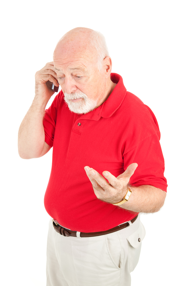 Senior man having an argument over his cellphone.  Isolated on white.