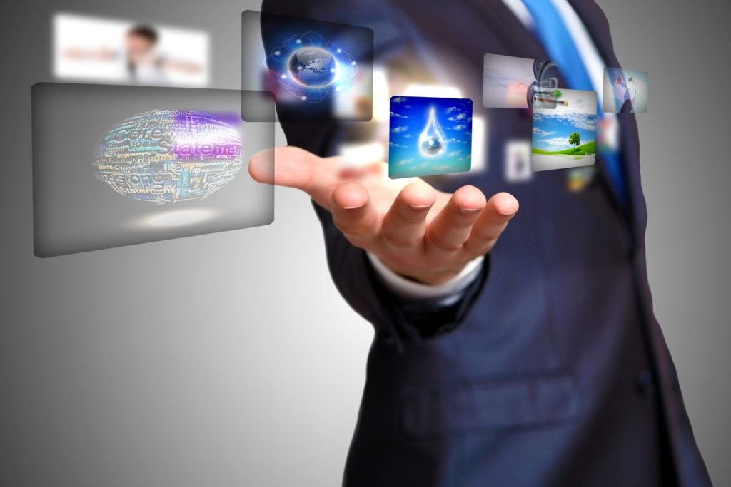 Man with digital screens floating above his hands displaying technologies