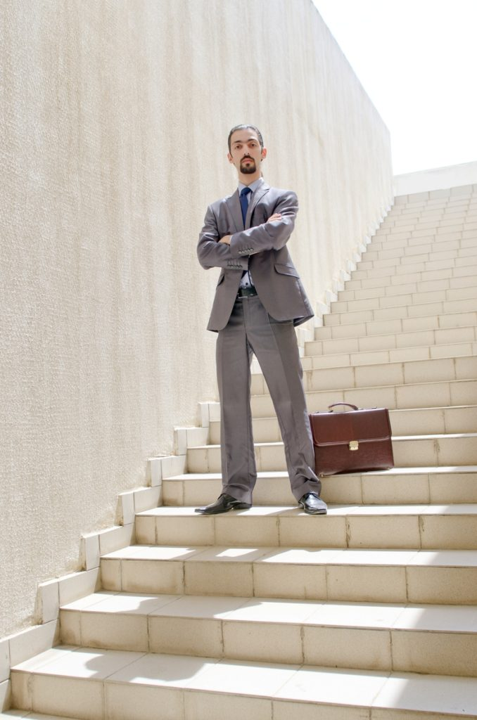 Businessman standing on steps with briefcase.