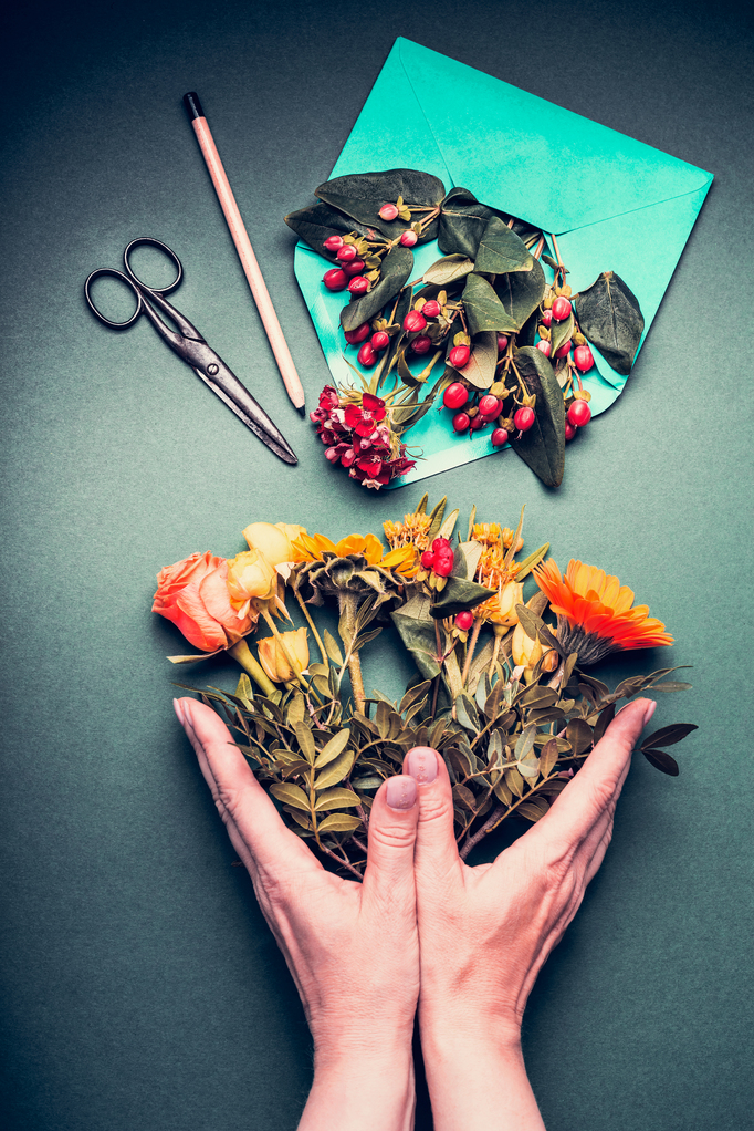 Female hands holding a Creative autumn flowers bouquet on florist workspace table background with opened envelop , shears , pencil, top view.