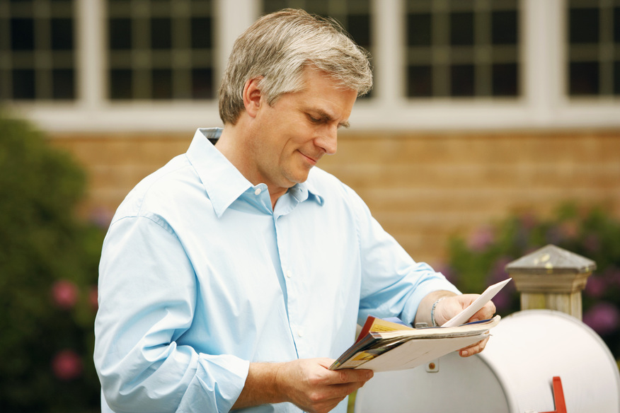 Man at his mailbox reading a letter he just received.