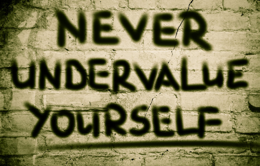 """never undervalue yourself"" painted on a brick wall"