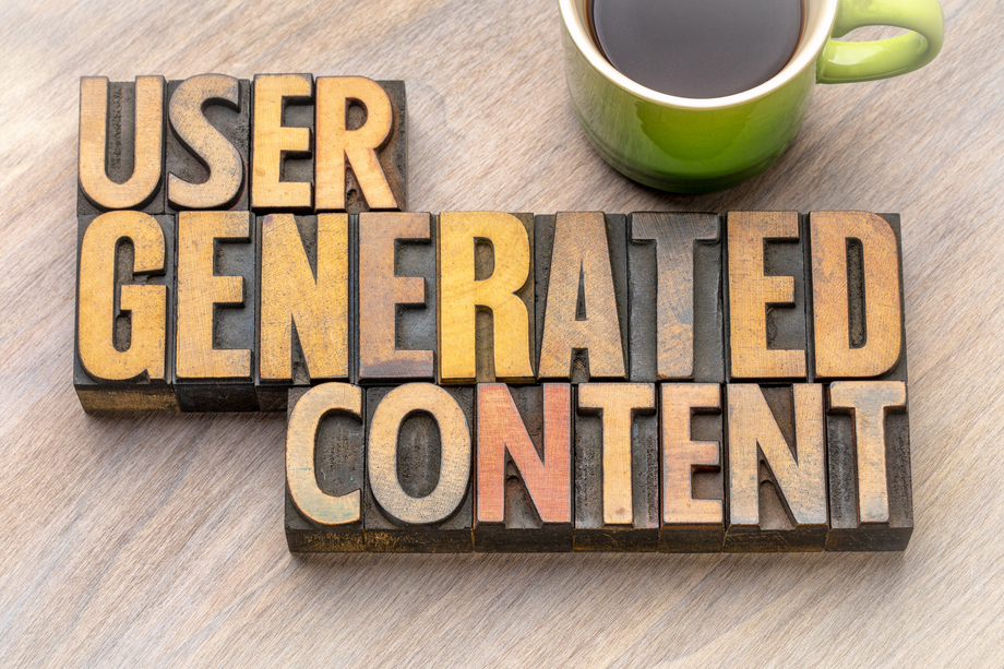"""User generated content"" carved in wood with a cup of coffee."