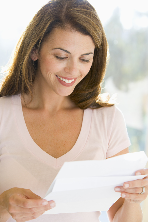 Woman reading physical newsletter from her mail